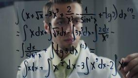 Manforskaren skriver den väsentliga likställanden på exponeringsglaset En matematiker löser ett matematiskt problem stock video