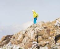 Manfotvandrare på överkanten av berget arkivbild