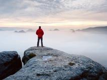 Manfotvandrare på bergmaximumet Förträfflig gryning i dimmigt landskap för höst Sol som döljas i moln royaltyfri foto