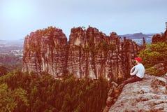 Manfotvandraren med det röda locket vaggar på och blickar på det skarpa berget arkivfoton