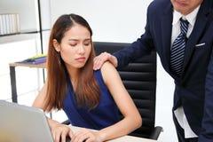 Manframstickande som trycker p? kvinnaskuldran i arbetsplats av kontoret sexuellt mobbningkontor royaltyfria foton