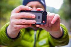 Manfrotto iPhone Lens Photographer. Oakridge, Oregon, USA - February 19,2014: Photographer using an iPhone 5S with Manfrotto lens attached outdoors royalty free stock photography