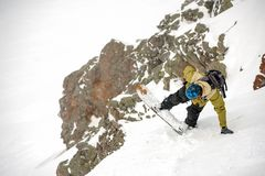 Manful snowboarder jumping down the slope in the mountain resort stock images