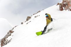 Manful snowboarder riding down the hill in the mountain resort royalty free stock images