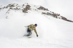 Manful snowboarder riding down the slope in the mountain resort stock photo