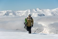 Manful snowboarder walking in the mountain resort stock photography