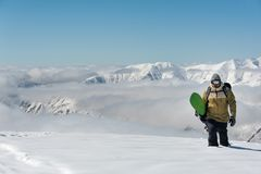 Manful snowboarder walking with the snowboard on the background stock image