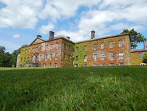 Mangårdsbyggnad med gräsmatta och blå himmel Arkivfoto