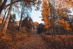 Mangårdsbyggnad med träd i höstfärg- och nedgångträd Gammalt viktorianskt spökat hus med spökar Övergett hus i höstträ arkivfoto