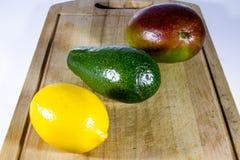 Manga, abacate e limão maduros em uma placa de corte foto de stock royalty free