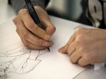 Manga artist drawing. Hands of a manga artist drawing a sketch royalty free stock image
