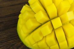 A manga cortou a vida tropical das vitaminas amarelas verdes vermelhas frescas maduras do cubo na madeira Imagens de Stock