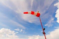 Manga de viento roja y blanca rayada contra el cielo azul Imagen de archivo