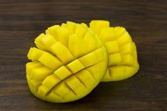 A manga dois cortou a vida tropical das vitaminas amarelas verdes vermelhas frescas maduras do cubo na madeira Imagem de Stock