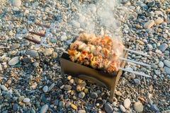 Mangal with shashlik on pebble beach Stock Images