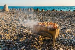 Mangal with shashlik on pebble beach Stock Photos