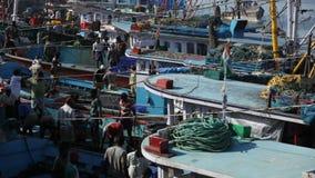 MANGALORE INDIEN -2011: Fiskare som överför fisklåset från havet till lastbilar på Oktober arkivfilmer