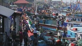 MANGALORE INDIEN -2011: Fiskare som överför fisklåset från havet till lastbilar på Oktober