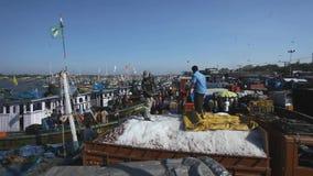 MANGALORE INDIEN -2011: Fiskare som överför fisklåset från havet till lastbilar på Oktober stock video