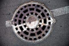 Mangat met metaaldekking in asfalt met witte weg die lijn merken royalty-vrije stock foto's