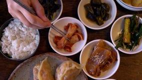 Mangeant Kimchi, plat coréen traditionnel servi avec de petites garnitures Clled Banchan Cuisine authentique asiatique clips vidéos