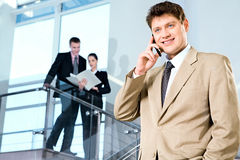 Manger with cellphone. Portrait of confident manager calling by cellphone on the background of people Stock Images