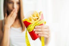 Manger de la nourriture Jolie jeune femme drôle avec des fritures images libres de droits