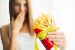 Manger de la nourriture Jolie jeune femme drôle avec des fritures photographie stock