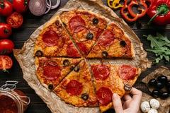 Manger de la pizza, vue supérieure Main prenant la tranche de pizza délicieuse chaude Ingrédients de pizza sur la table en bois Photo libre de droits