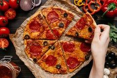 Manger de la pizza, vue supérieure Main prenant la tranche de pizza delisious chaude Ingrédients de pizza sur la table en bois Photographie stock