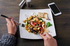Manger de la salade avec le poulpe et les légumes POV image libre de droits