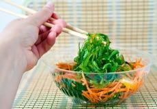 Manger de la salade de Wakame Photographie stock