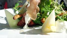 Manger de la salade de laitue, de melon et de jambon au restaurant banque de vidéos