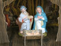 Manger scene. Vintage figurenes of Mary, Joseph and Baby Jesus in a stable Stock Photography