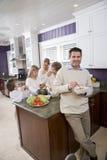Mangeur d'hommes dans la cuisine avec le famille à l'arrière-plan Image libre de droits