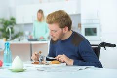 Mangeur d'hommes handicapé avec l'épouse à l'arrière-plan Images libres de droits