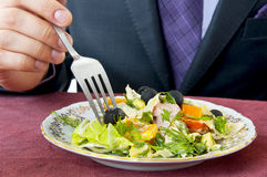 Mangeur d'hommes. Main avec la fourchette. Salade sur le plan rapproché de plaque Photo stock
