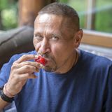 Mangeur d'hommes d'une cinquantaine d'années heureux une fraise rouge mûre, portrait en gros plan Image libre de droits