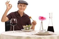 Mangeur d'hommes une salade et fabrication d'un geste correct Photo libre de droits