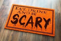 Mangez, boisson et soyez accueil effrayant Mat On Wood d'orange de Halloween photographie stock