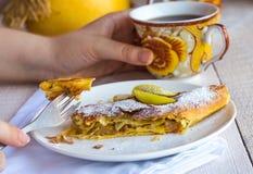 Mangez du strudel aux pommes d'un plat blanc, mains Photographie stock