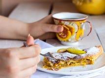 Mangez du strudel aux pommes d'un plat blanc, mains, fourchette Images stock