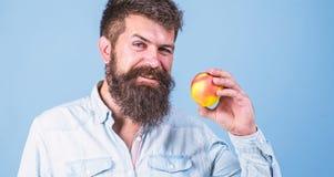 Mangez sain Homme avec la main de fruit de pomme de prise de hippie de barbe Faits de nutrition et prestations-maladie Fruit popu photographie stock