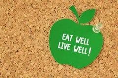 Mangi bene, viva bene! scritto sulla nota di carta a forma di mela sul pinbo fotografia stock libera da diritti