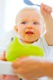 Mangi il bambino adorabile spalmato che gioca con il cucchiaio immagine stock libera da diritti