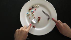 Mangi le pillole dal piatto con un coltello e una forcella Il concetto di peso di perdita con le pillole o uso regolare delle pil stock footage