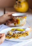 Mangi lo strudel alle mele su un piatto bianco, le mani, forcella Fotografie Stock Libere da Diritti