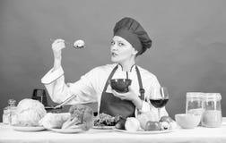 Mangi sano Razione sana Gusto del fungo del cappello di usura della ragazza e di prova del grembiule Cucchiaio professionale dell immagini stock libere da diritti