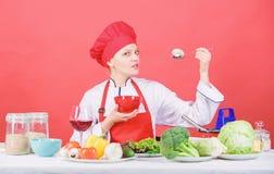 Mangi sano Razione sana Gusto del fungo del cappello di usura della ragazza e di prova del grembiule Cucchiaio professionale dell fotografia stock