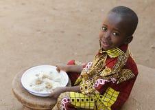 Mangiando in Africa - piccolo simbolo nero di fame del ragazzo Fotografia Stock Libera da Diritti